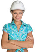 Pretty girl in shirt and white helmet standing with crossed arms — Stock Photo