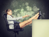 Businesswoman in office chair with her feet up on anything — Stock Photo