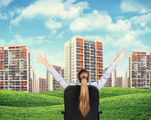 Businesswoman sitting on office chair. Green hills with buildings and sky — Stock Photo