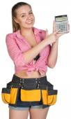 Woman in tool belt showing calculator — Stock Photo