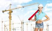 Woman in hard hat with large builders level on her shoulder — Stock fotografie
