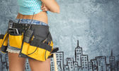 Woman in tool belt against stone wall with sketch of city on it — Stock fotografie