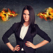 Angry woman standing with arms akimbo, fire from ears. Concrete wall in background — Stock Photo #66143361