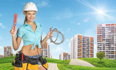 Woman in helmet holds adjustable spanner and two flexible hose. Green hills, road, buildings as backdrop — Stock Photo