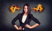 Angry woman standing with arms akimbo, fire from ears. Concrete wall in background — Stock Photo