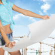 Woman holds white paper. Cropped image. Tower cranes and sky as backdrop — Stock Photo #66194569