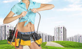 Woman holding two flexible hose. Cropped image. Green hills with road and buildings on background — Stock Photo