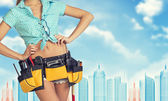 Woman in tool belt stands back, hands on hips. Cropped image. Wire-frame buildings as backdrop — Stock Photo