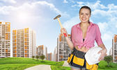 Woman in tool belt holding hammer and helmet. Green hills, road, buildings as backdrop — Stock Photo
