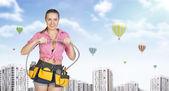 Woman in tool belt connects two flexible hoses. Buildings with air balloons as backdrop — Stock Photo
