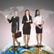 Business womens in suits, blouses, skirts, smiling and looking at camera. Against background of world map — Stock Photo #67867693