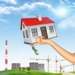 Hand holding house and bunch of keys. In background tower crane, chimney, green hill with grass, trees — Stock Photo #67868001
