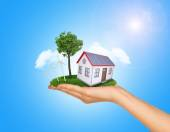 Hand holding house on green grass with tree, solar panels, wind turbine. Background clouds, blue sky — Stock Photo