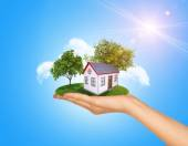Hand holding house on green grass with tree, solar panels. Background clouds, blue sky — Stock Photo