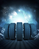 Wedge of new car wheels. Background is night sky and stripes at bottom — Stock Photo