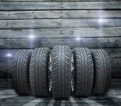 Wedge of new car wheels. Background is wooden boards — Stock Photo