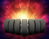 Wedge of new car wheels. Red background is galaxy and stripes at bottom — Stock Photo
