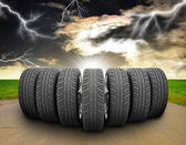 Wedge of car wheels. Road, roadsides, grass field and stormy sky in background — Stock Photo