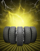 Wedge of new car wheels. Yellow background with lightning and stripes at bottom — Stock Photo