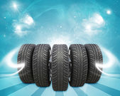 Wedge of new car wheels. Blue background is magic sky and stripes at bottom — Stock Photo