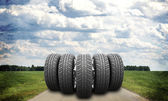 Wedge of new car wheels on road stretches into the distance — Stock Photo