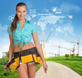 Girl builder in toolbelt holding tools — Stock fotografie
