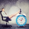 Businesswoman sits in chair. Put your feet up on big red alarm clock — Stock Photo #69315865
