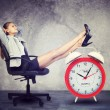 Businesswoman sits in chair. Put your feet up on big red alarm clock — Stock Photo #69316013