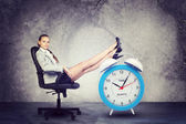 Businesswoman sits in chair. Put your feet up on big red alarm clock — Stock Photo