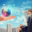 Business woman sitting in chair and hand holding globe — Stock Photo #70715687