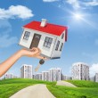 House and keys in womans hand on cityscape — Stock Photo #71615097