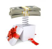 Gift box with red band and dollar packs on spring — Stock Photo