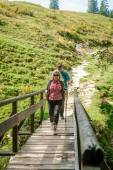 Two hiker on a wooden bridge — Stock Photo