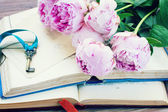 Pile of old books with pink flowers — Stock Photo