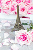 Pink  roses  with eiffel tour on table — Stock Photo