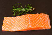 Salmon steak with twig of rosemary — Stock Photo