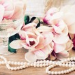 Magnolia flowers with pearls on wooden table — Stock Photo #57841827