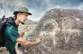 Man touching petroglyph with goat — Stock Photo