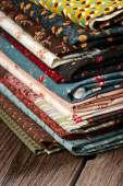Heap of cloth fabrics on wooden table — Stock Photo