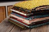 Heap of cloth fabrics on wooden table — Stock Photo