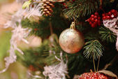 Christmas background with a gold ornament, berries and fir in snow — Stock Photo