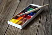 Box of professional watercolor on wood background — Stock Photo