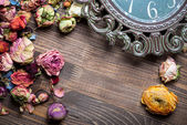 Abstract holiday frame with rose petals and dried flowers on old wooden plates. — Stock Photo