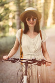 Girl on bicycle in forest — Stock Photo