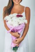 Young woman with bouquet of flowers over white background. Close — Stok fotoğraf