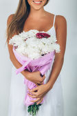 Young woman with bouquet of flowers over white background. Close — Fotografia Stock