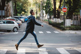 Young man cross the street — Stock Photo