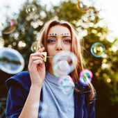 Young woman portrait blowing soap bubbles — Photo