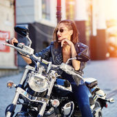 Biker girl in a leather jacket on a motorcycle — Stock Photo