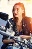 Biker girl in a leather jacket on a motorcycle — Стоковое фото
